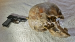 Walther PPK hand pistol with the Skull remains of a former Ustacha militia- Black Legion officer, who had been severely beaten and then executed with his own PPK, showing the entry hole and the path the bullet would have taken