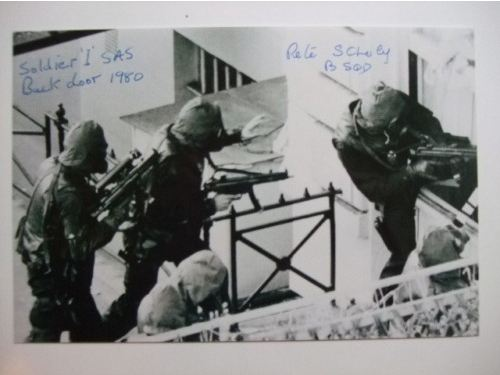 Personally signed (and original) signatures on this 9x6 print which depicts the SAS soldier known as Soldier 1 who survived ther Battle of Mirbat , was an Iranian Embassy Siege Assulter and parachuted into the seas off the Falklands during that Conflict with the Argentinians, assulting the Embassy from the back plus also signed by Pete Scholey (author of the Joker and SAS Heroes) who was with the Advance Party and helped install surveillance equipment