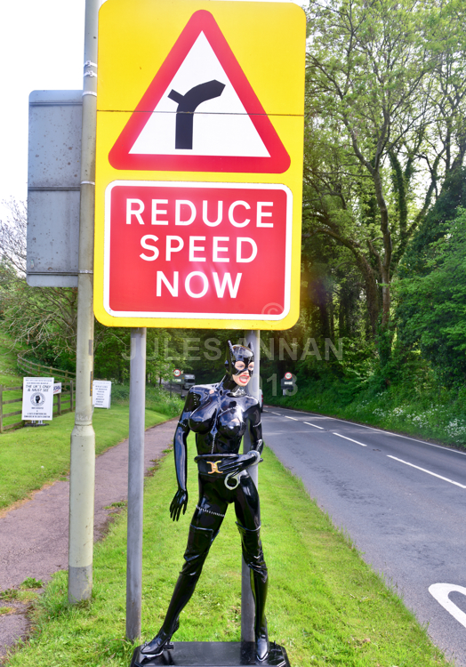 """Andy Jones, from the Crime Through Time Collection puts a  lifesize fetish model of the Catwoman (Michelle Pheiffer) from the Batman Returns film (1992)  under """" REDUCE SPEED NOW """" sign outside the Museums entrance at  Littledean Jail in the Forest Of Dean, Gloucestershire, UK in an effort to slow the speeding traffic.  Andy said """"She simply sets the tone on what to expect in the Uk's most politically incorrect tourism attraction..... at the same time helping the local authority to reduce speeding through the Forest Of Dean ..... he also s"""