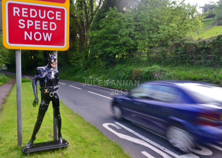 "Andy Jones, from the Crime Through Time Collection puts a  lifesize fetish model of the Catwoman (Michelle Pheiffer) from the Batman Returns film (1992)  under "" REDUCE SPEED NOW "" sign outside the Museums entrance at  Littledean Jail in the Forest Of Dean, Gloucestershire, UK in an effort to slow the speeding traffic.  Andy said ""She simply sets the tone on what to expect in the Uk's most politically incorrect tourism attraction..... at the same time helping the local authority to reduce speeding through the Forest Of Dean ..... he also says that every home should have one !!!"""