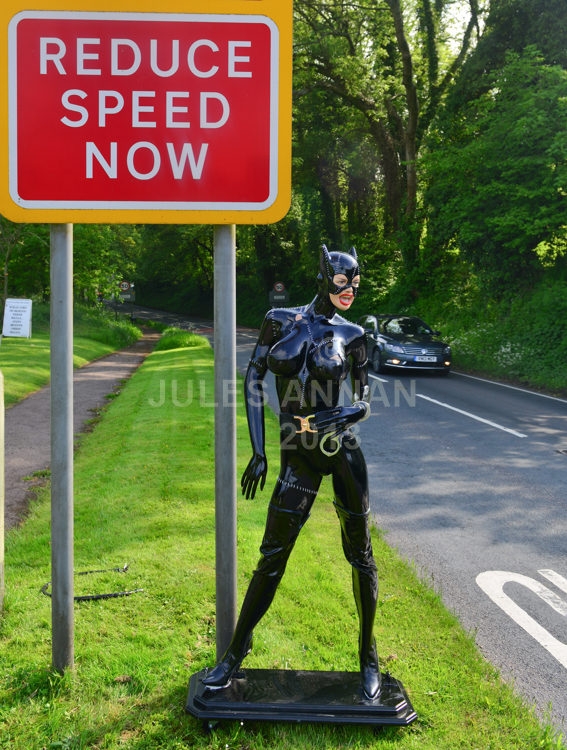 """Andy Jones, from the Crime Through Time Collection puts a  lifesize fetish model of the Catwoman (Michelle Pheiffer) from the Batman Returns film (1992)  under """" REDUCE SPEED NOW """" sign outside the Museums entrance at  Littledean Jail in the Forest Of Dean, Gloucestershire, UK in an effort to slow the speeding traffic.  Andy said """"She simply sets the tone on what to expect in the Uk's most politically incorrect tourism attraction..... at the same time helping the local authority to reduce speeding through the Forest Of Dean ..... he also says that every home should have one !!!"""""""